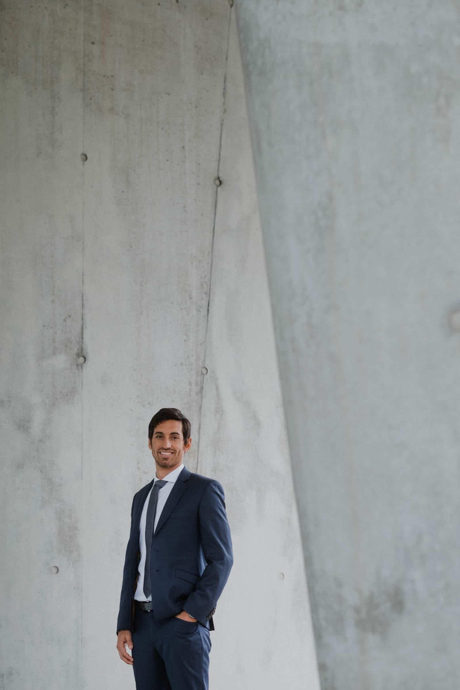 ein Mann, der einen Anzug und eine Krawatte trägt, steht vor einer hellen Betonwand, er hält eine Hand in seiner Hosentasch, er schaut direkt in die Kamera
