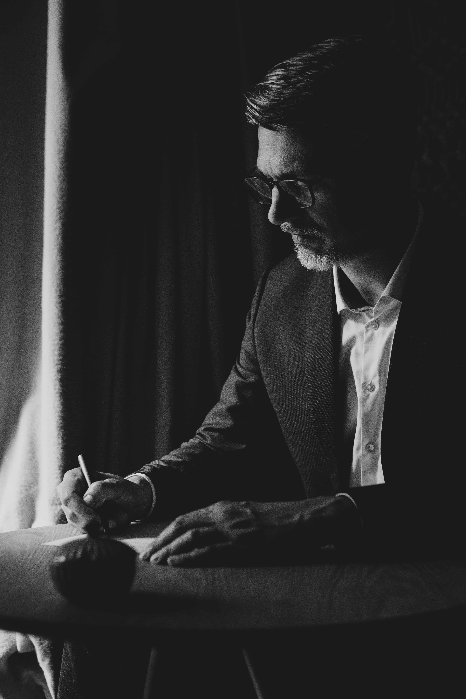 ein Mann in Sakko und Hemd sitzt an einem Tisch,er schreibt auf einem Papier, er schaut konzentriert auf das Papier