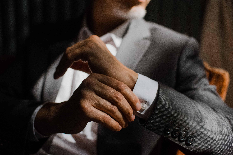 ein Mann hält seine Hand an die Manschette seines Hemd, er sitzt auf einem Holzstuhl, die Sonne scheint auf sein Sakko
