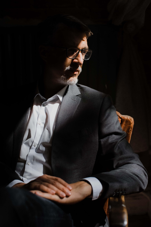 ein Mann trägt ein Sakko und ein Hemd, er sitzt auf einem Holzstuhl, er schaut zur Seite, die Sonne scheint ihm ins Gesicht