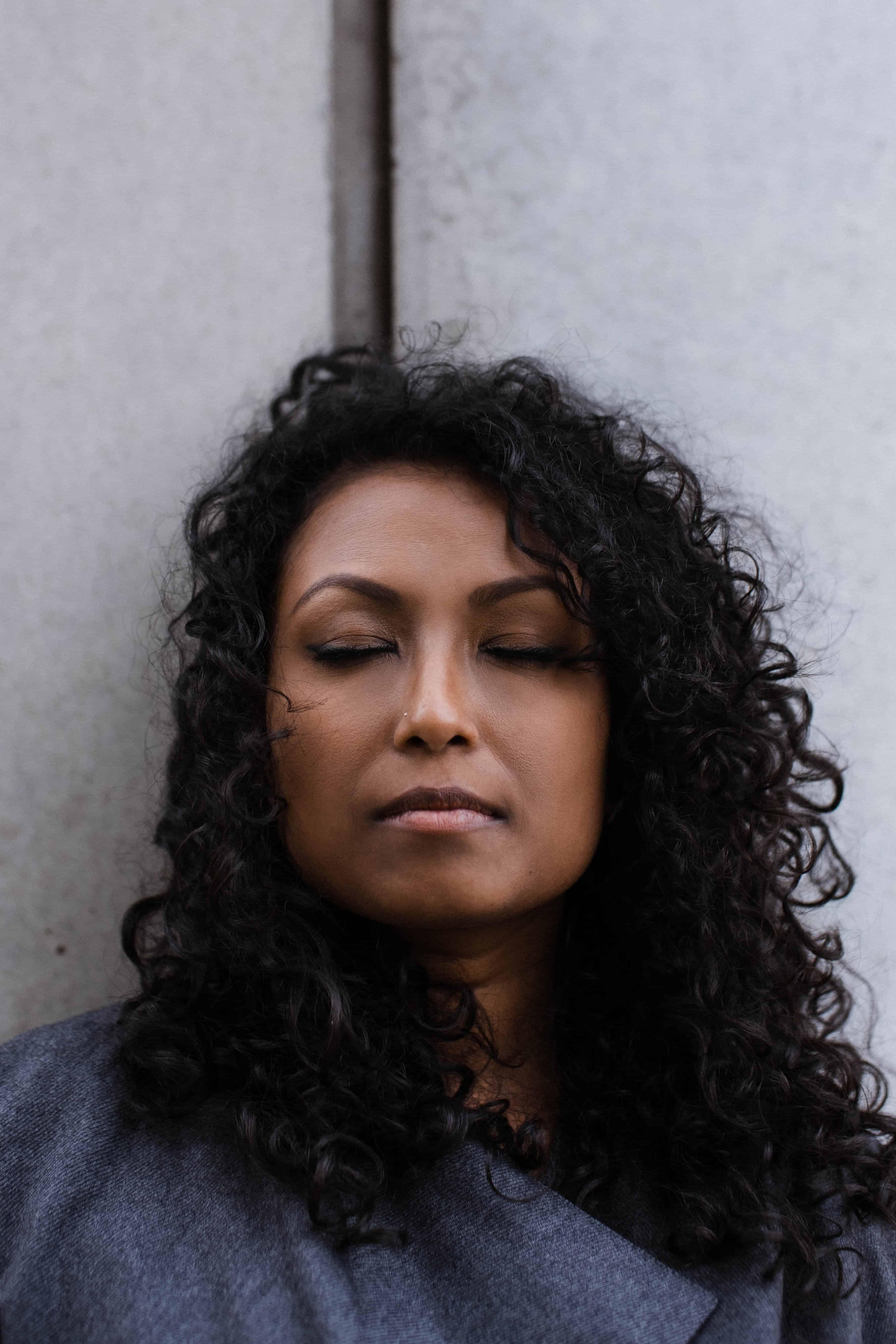 Nahaufnahme einer Frau, die an einer hellen Betonwand lehnt, sie hat geschlossene Augen