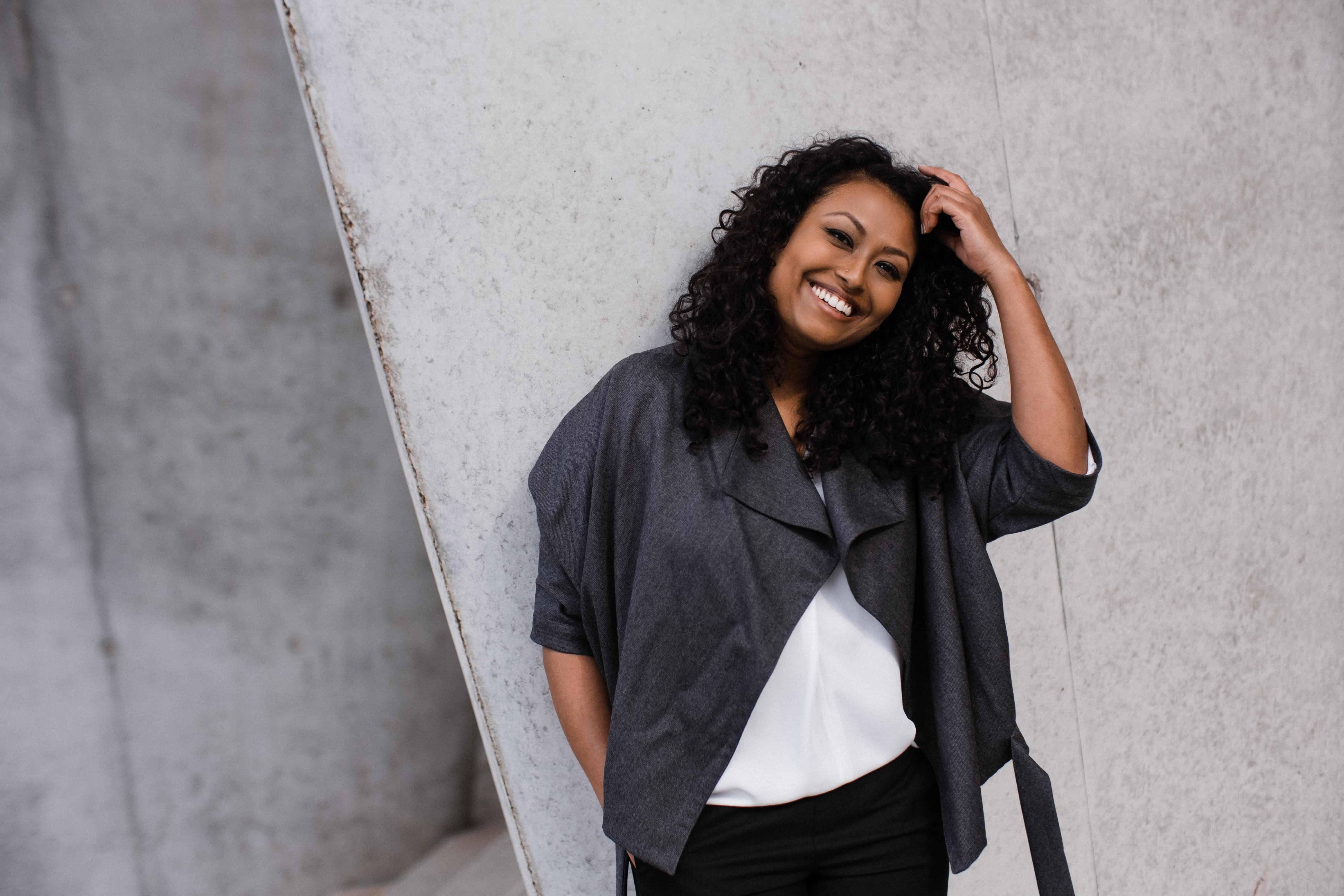 eine Frau lehnt an einer hellen Betonwand, sie hält sich mit einer Hand in ihr lockiges Haar, sie lacht
