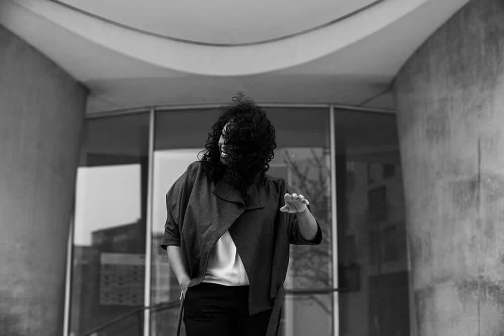 eine Frau steht vor einer Eingangstür, die aus Glas ist, ihre Haare wehen ihr in Gesicht, eine Hand hält sie nach oben