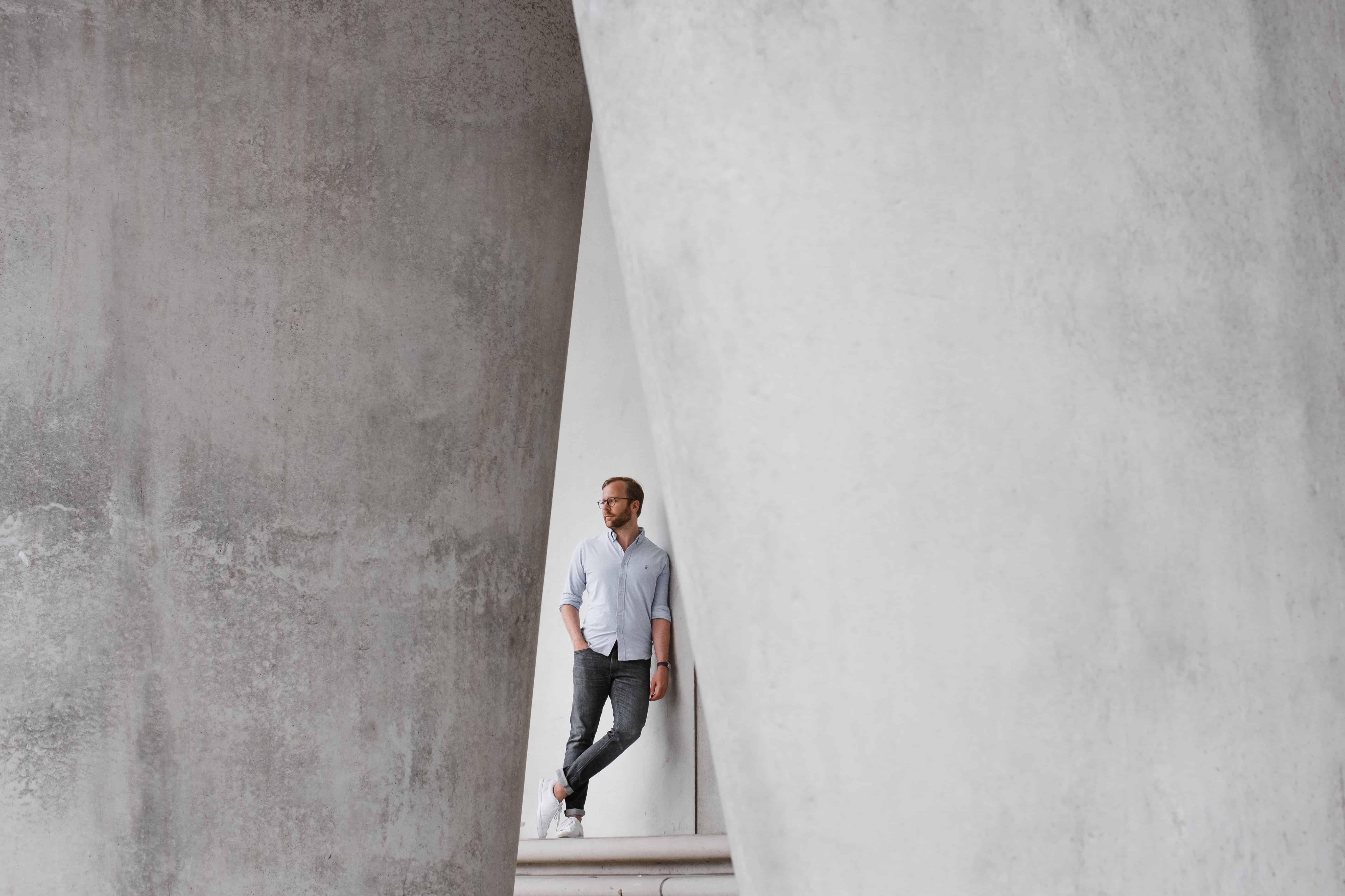 ein Mann lehnt seitlich an einer Betonwand, eine Hand hält er in die Hosentasche