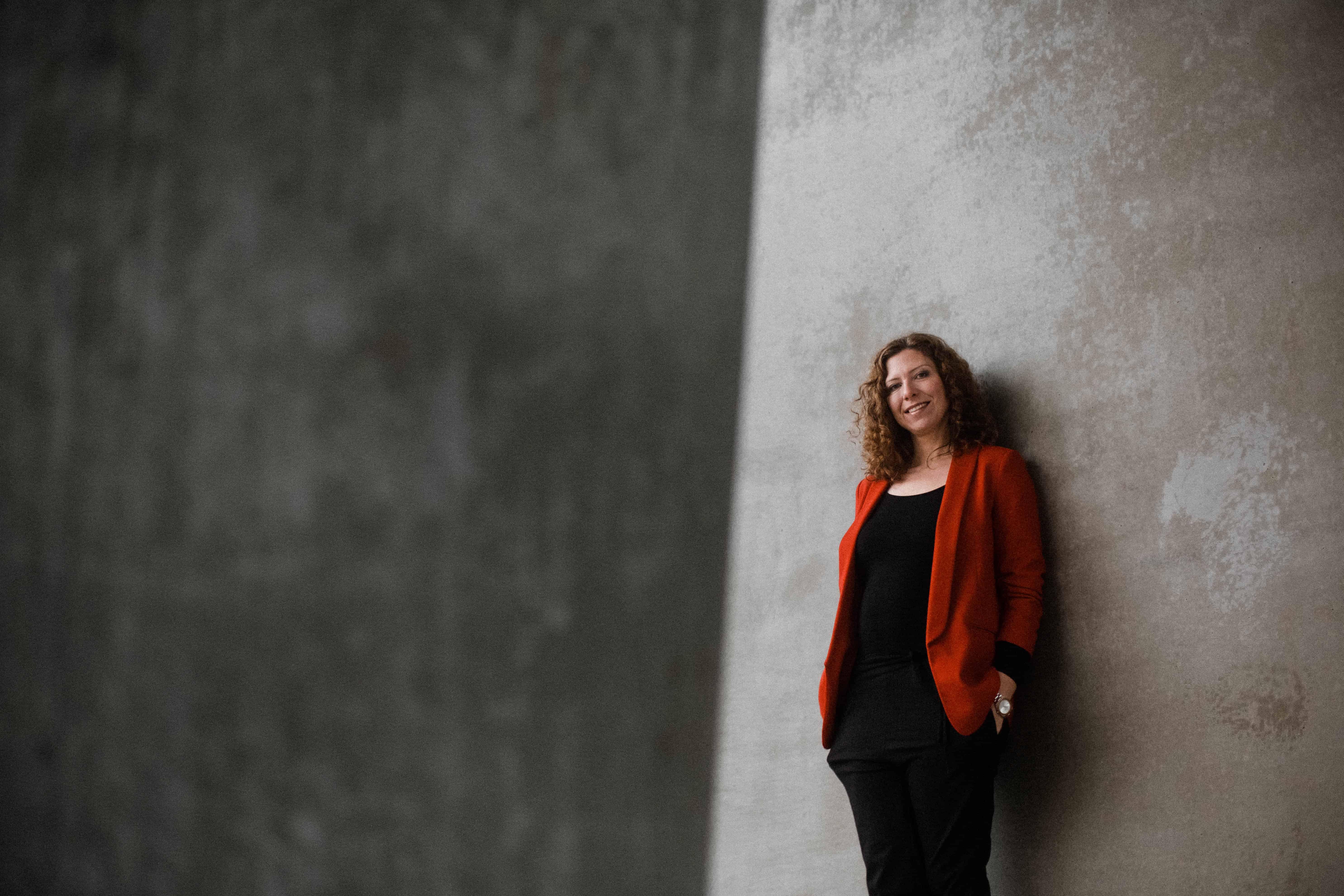 eine Frau lehnt an einer hellen Betonwand, sie hält ihre Hände in den Hosentaschen, sie schaut direkt in die Kamera