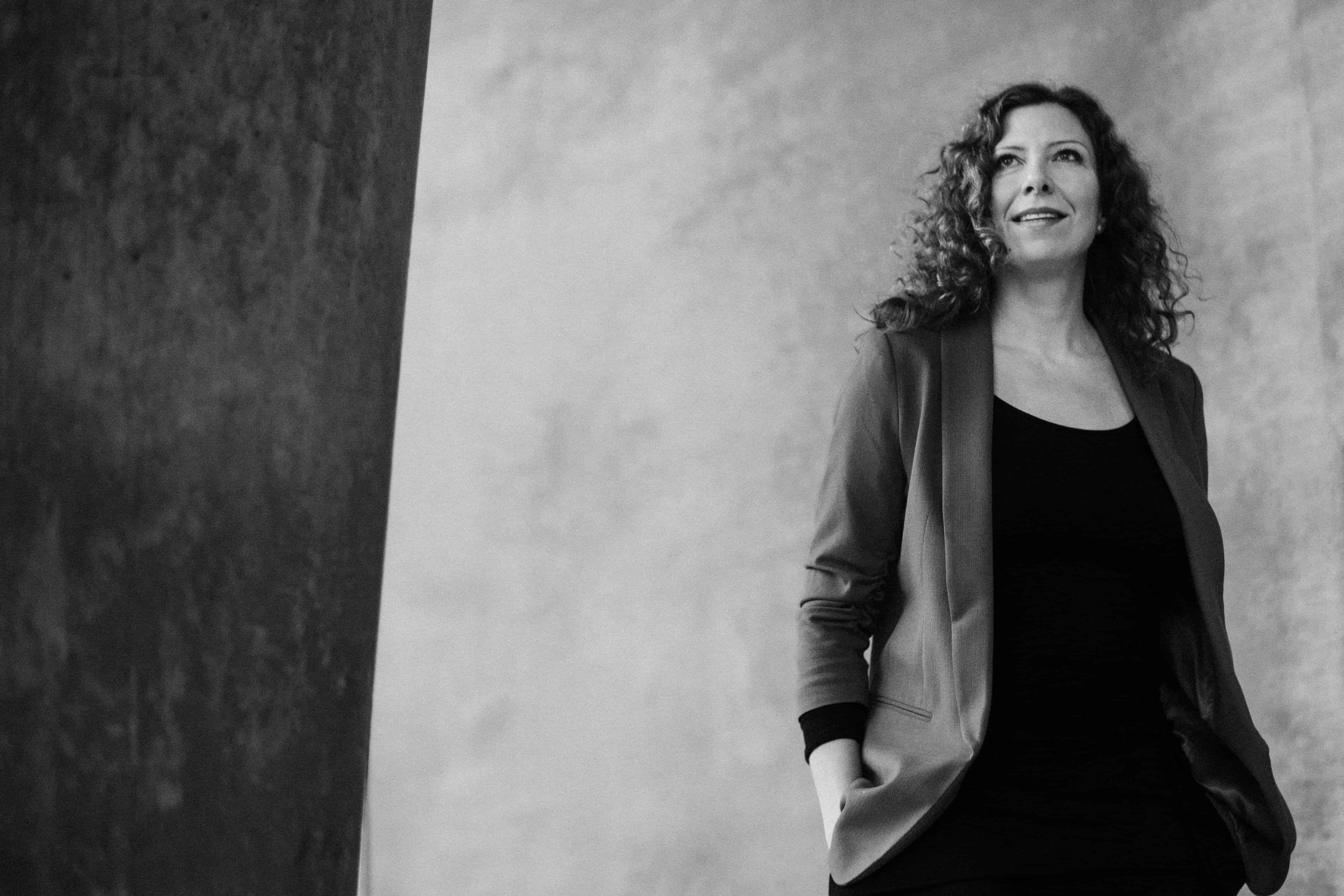 eine Frau steht vor einer hellen Betonwand, sie hält ihre Hände in den Hosentaschen und schaut in die Ferne