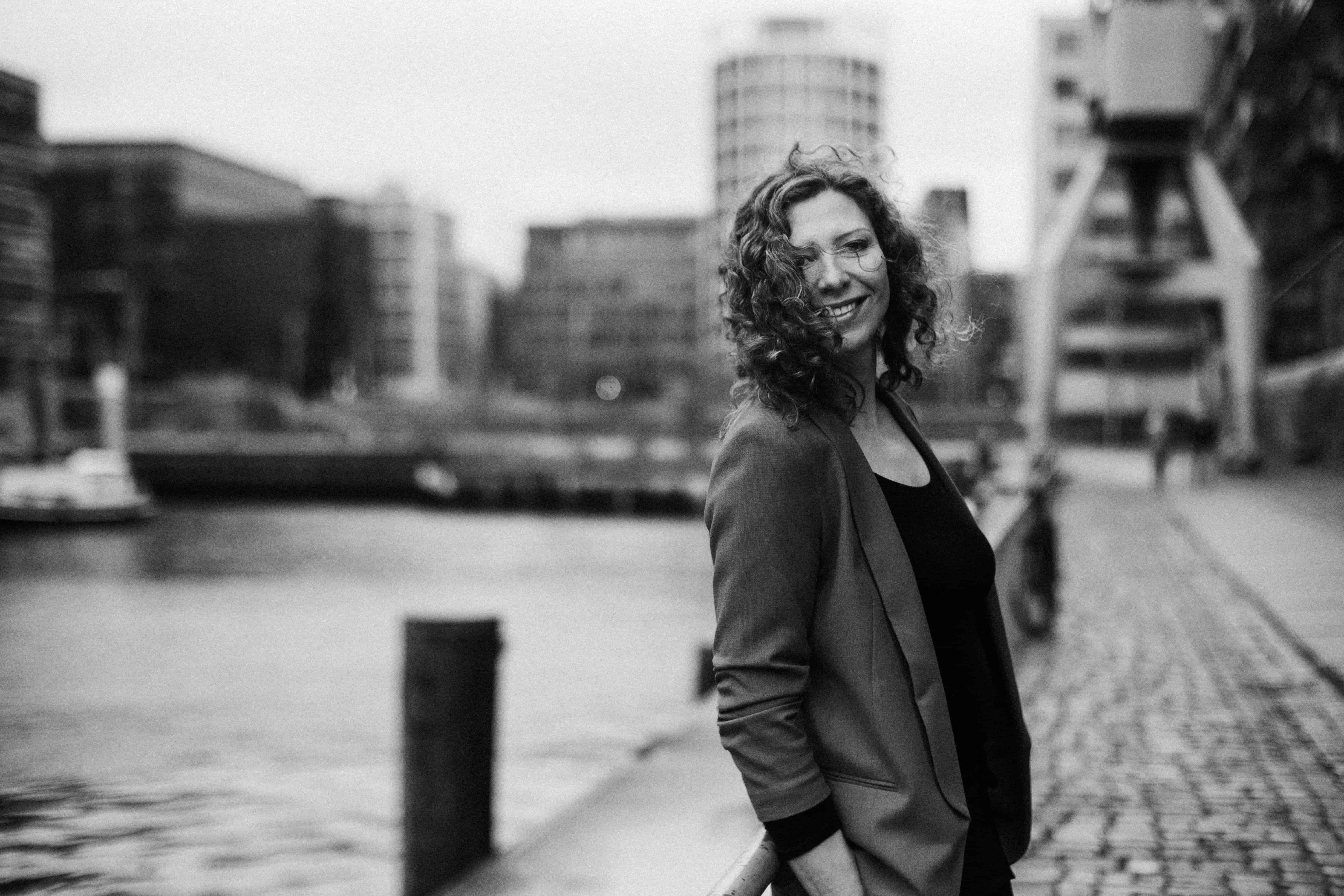 eine Frau steht im Hafen von Hamburg, sie steht seitlich zu dem Kanal, ihre Hände hält sie in den Hosentaschen, im Hintergrund ist die Stadt Hamburg zu sehen