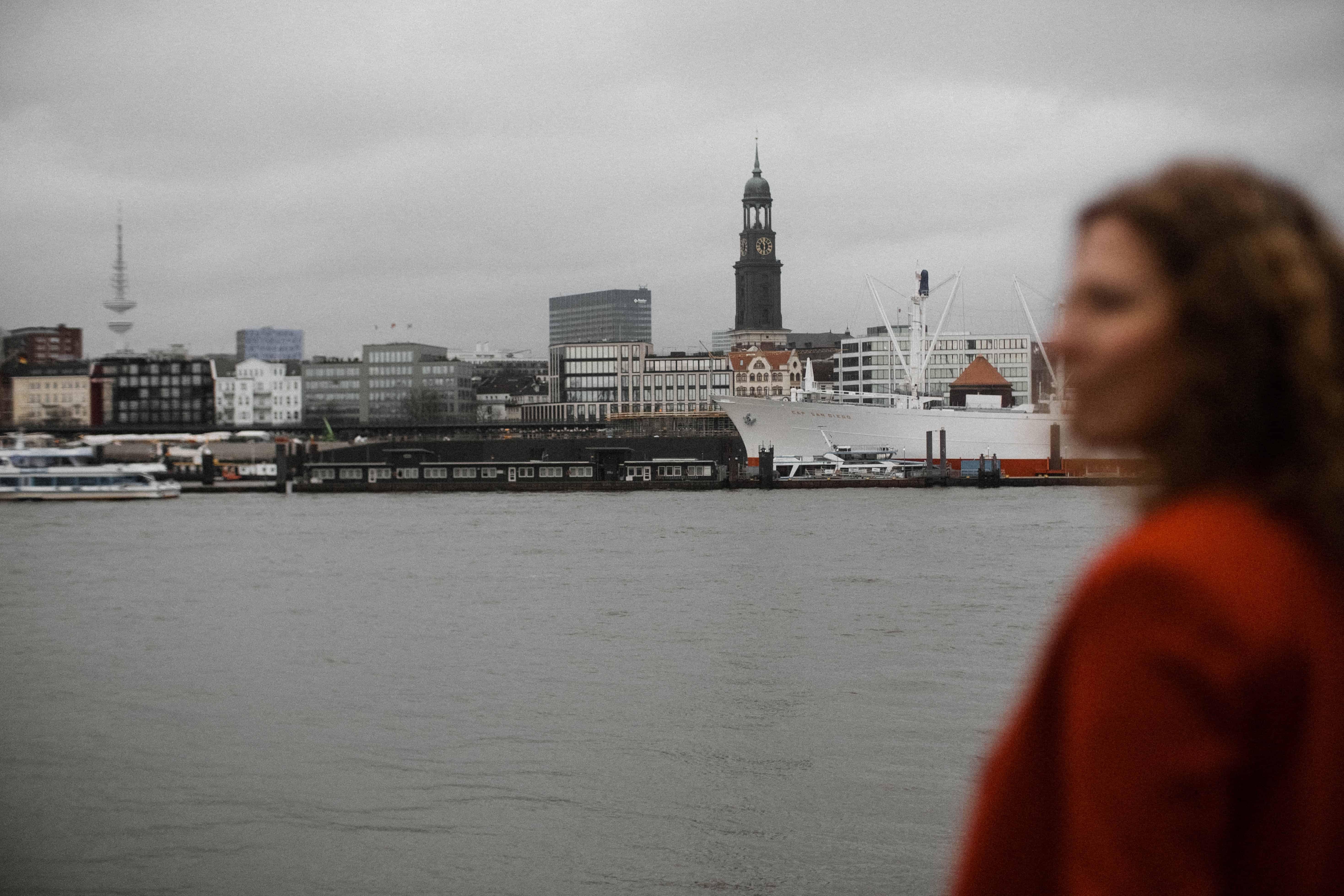 eine Frau ist im Vordergrund, sie schaut zur Seite, im Hintergrund ist der Hafen von Hamburg zu sehen