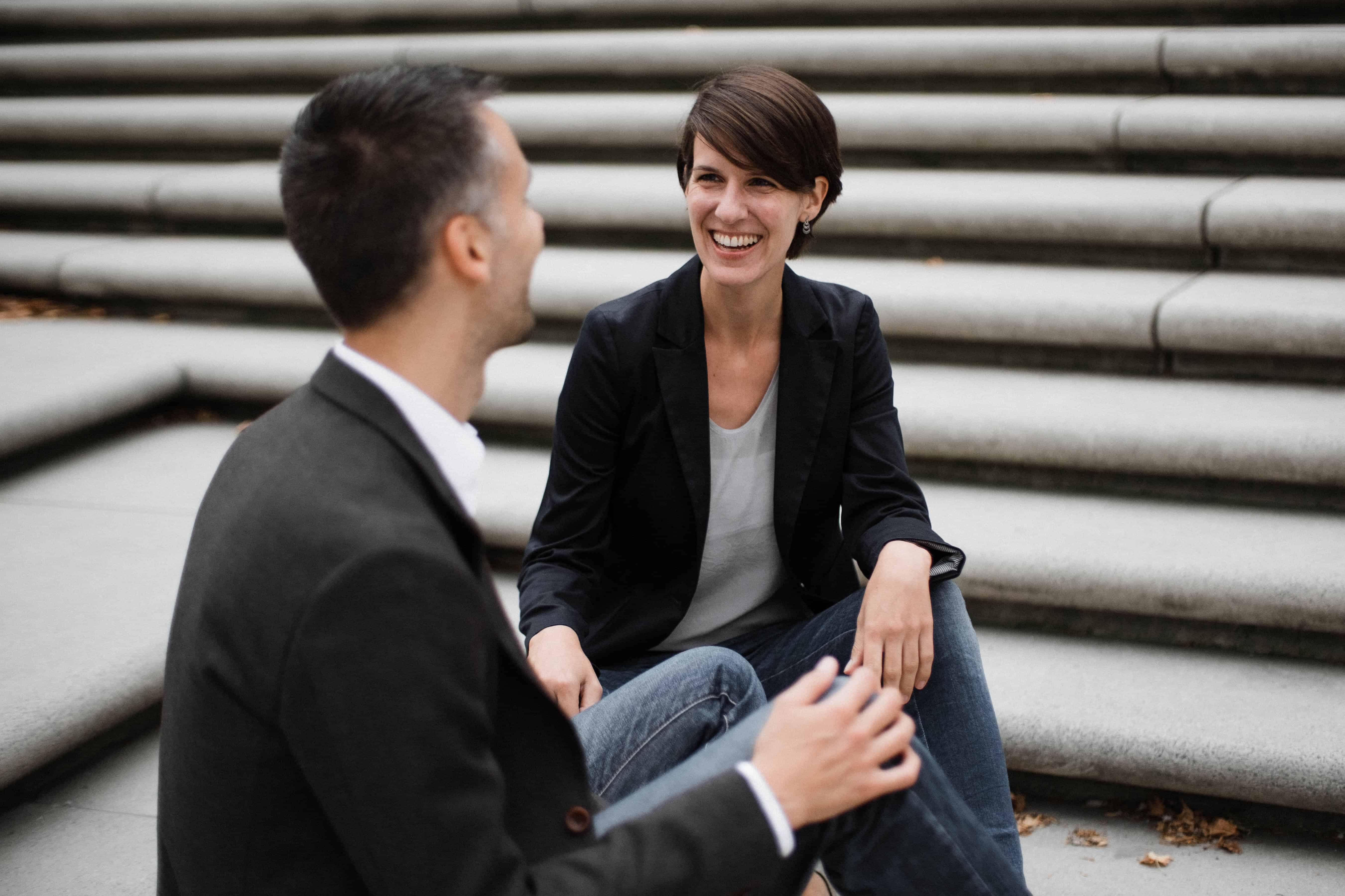 ein Mann und eine Frau sitzen auf einer Betontreppe, sie sind zueinander gerichtet& unterhalten sich