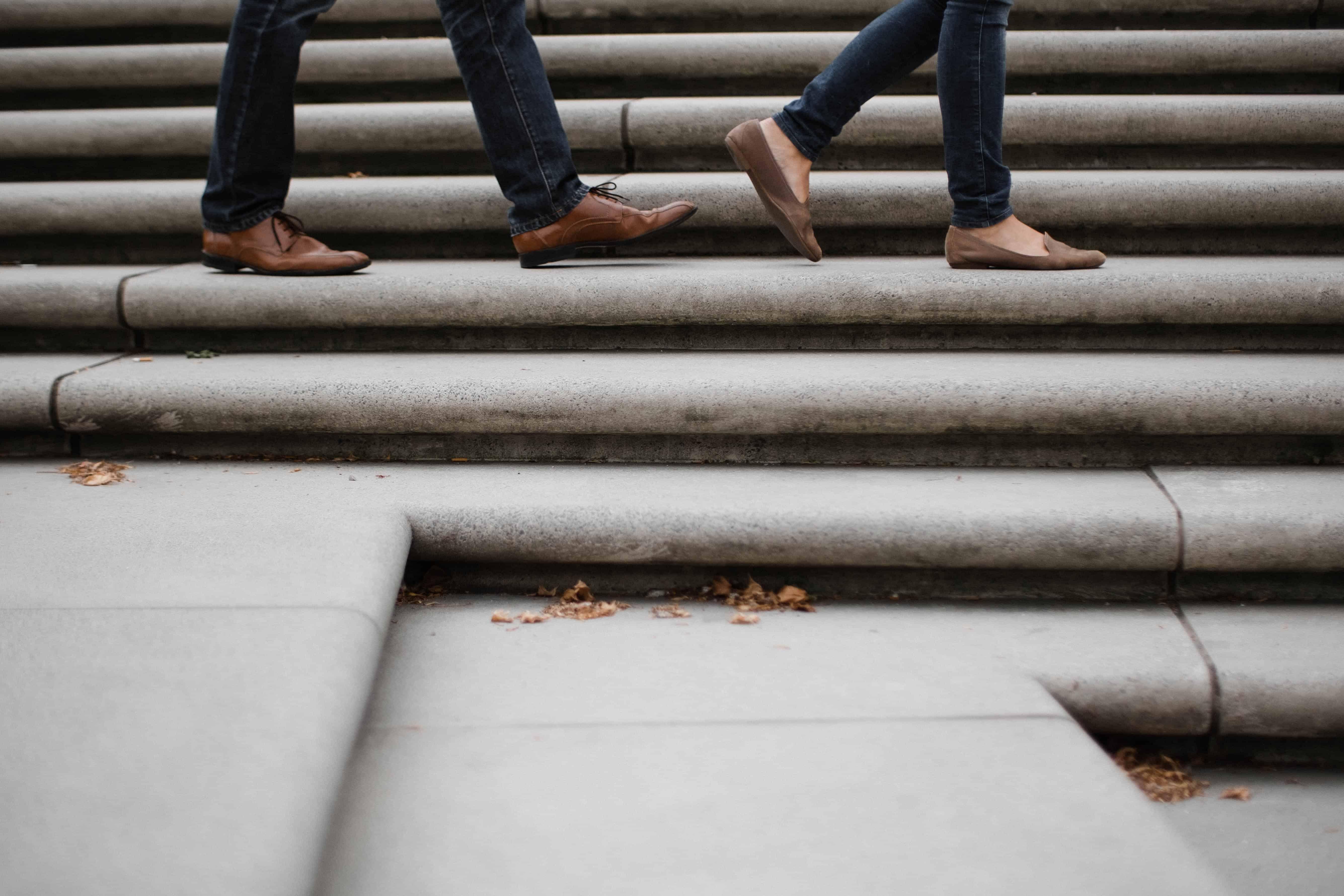 auf einer Betontreppe laufen 2 Personen, man sieht nur den unteren Teil der Beine