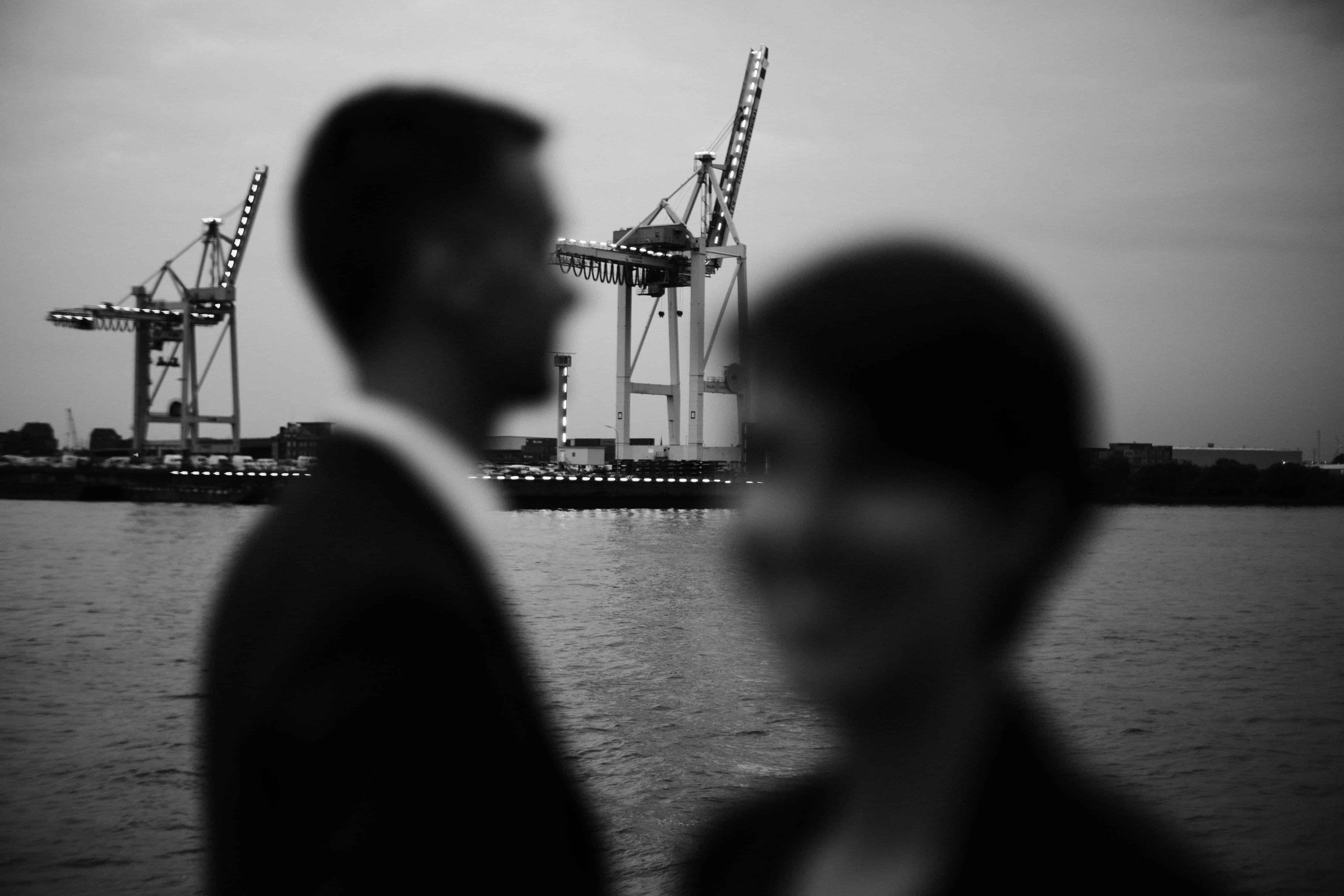 ein Mann und eine Frau stehen am Hafen in Hamburg, sie stehen nebeneinander und schauen in entgegengesetzte Richtungen, im Hintergrund ist der Containerhafen zu sehen
