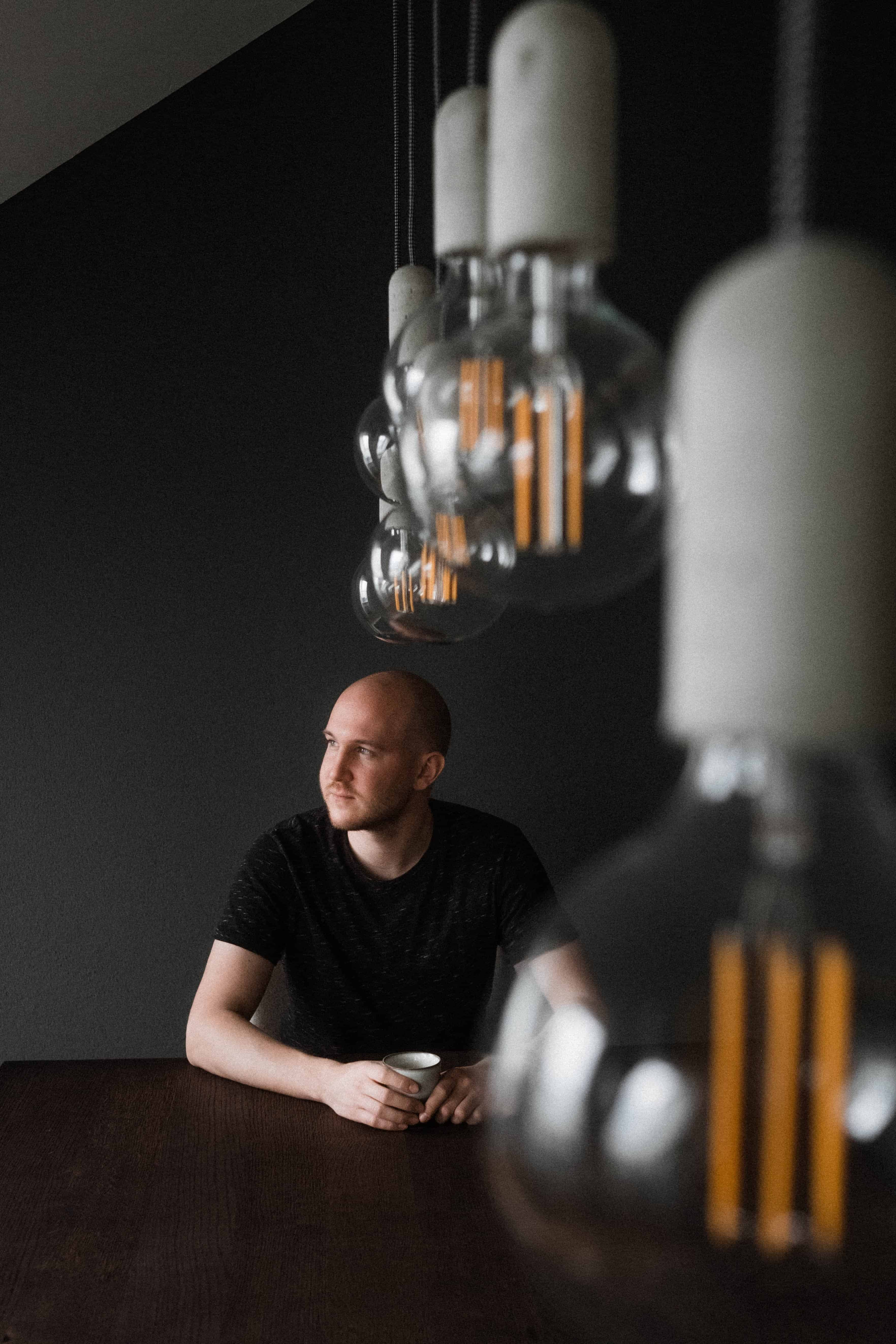 ein Mann sitzt vor einem schwarzen Hintergrund an einem schwarzen Tisch in einem Raum, vor ihm steht eine Tasse, die er mit beiden Händen hält, im Vordergrund hängen Vintage- Glühbirnen
