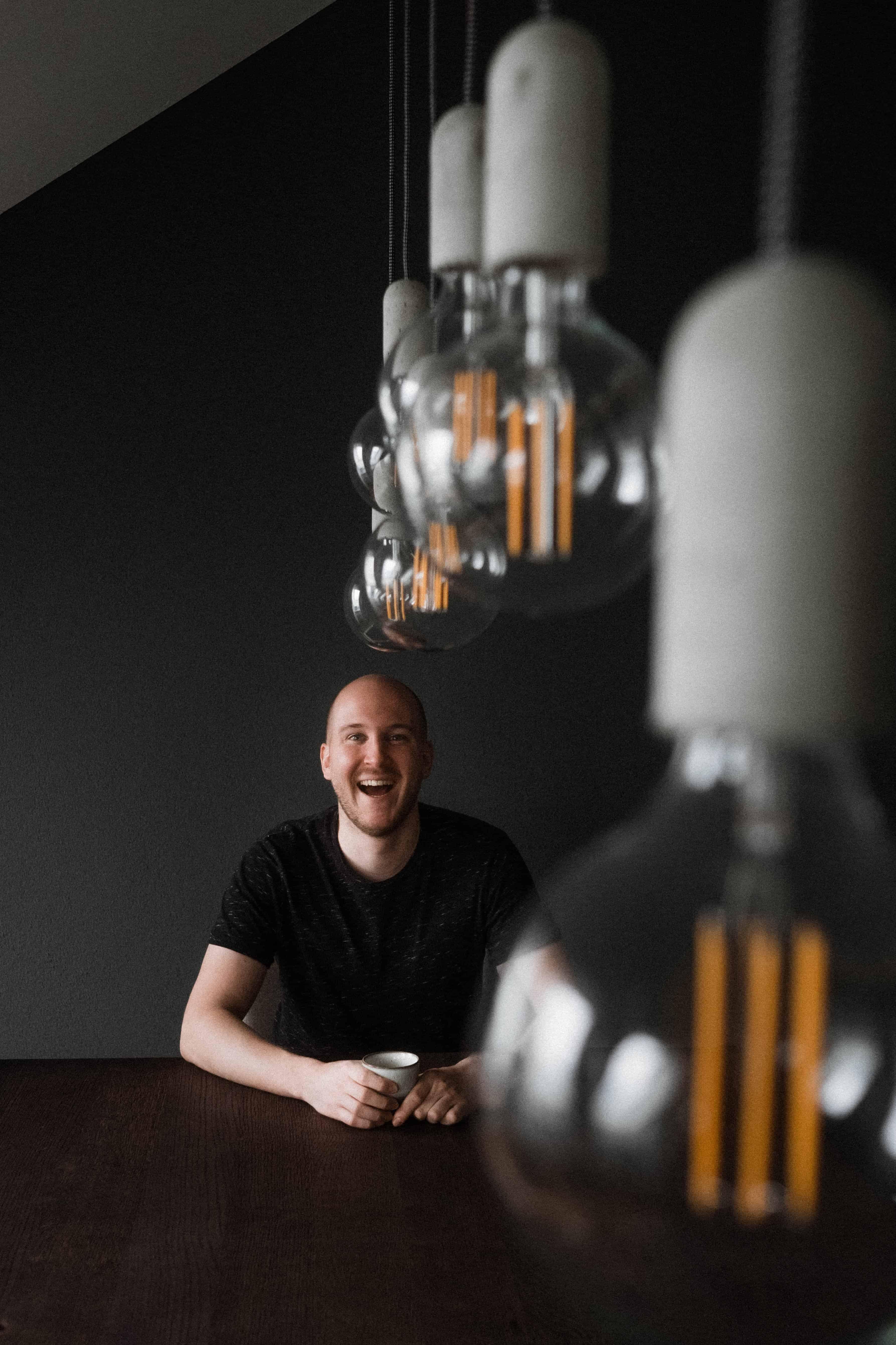 ein Mann sitzt vor einem schwarzen Hintergrund an einem schwarzen Tisch in einem Raum, vor ihm steht eine Tasse, die er mit beiden Händen hält, im Vordergrund hängen Vintage- Glühbirnen, er lacht direkt in die Kamera