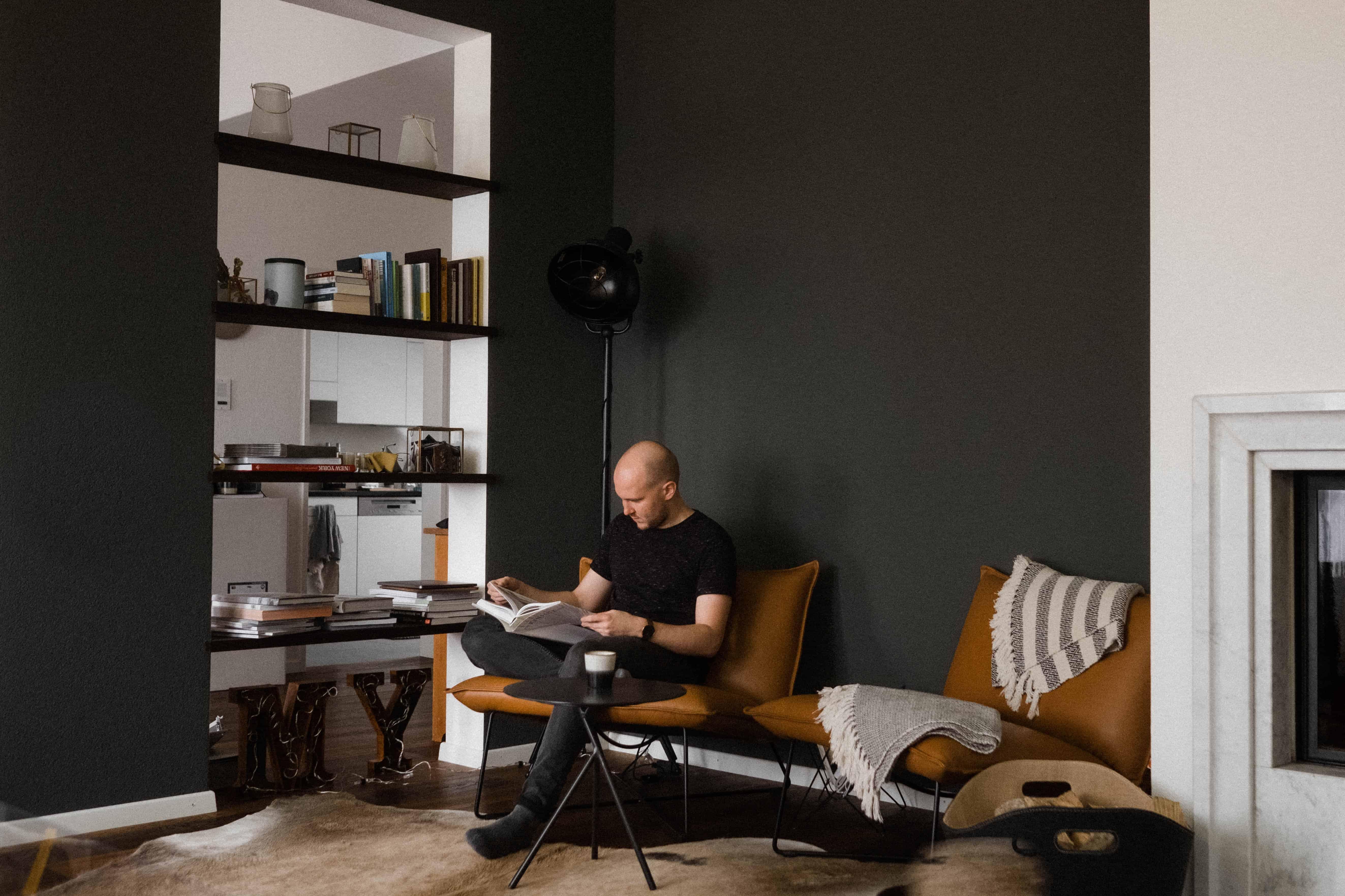 ein Mann sitzt in einem Wohnzimmer auf einem Ledersessel, er liest in einem Buch, neben ihm steht ein offenes Regal, in dem Bücher stehen